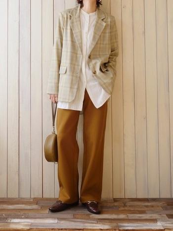黄土色のリラックスパンツとシャツ、チェックのジャケットでメンズライクな大人コーデ。ジャケットは同系色の淡いイエローが入っているのと、小物もブラウン系でまとめているのでスッキリとした印象に。かっこいい大人の雰囲気を演出しています。