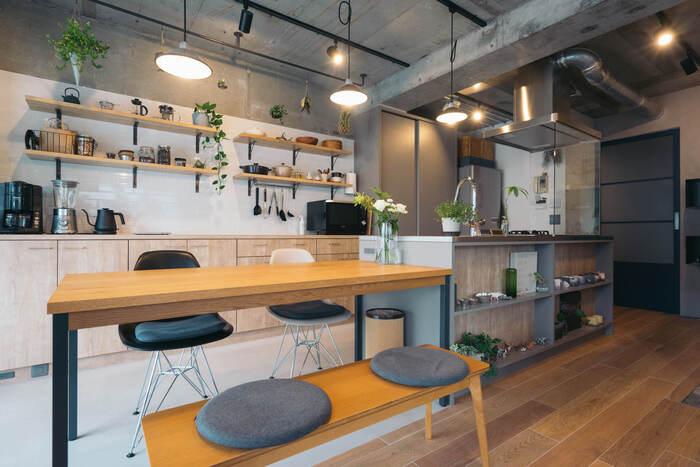 スタイリッシュなアイランドキッチンが印象的なこちらのお部屋。ナチュラルカラーの家具と、コンクリートの無機質な壁、グリーンの組み合わせがバランス良くおしゃれです。