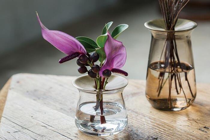 ガラスの透明感と真鍮のプレートの鈍い光のコントラストが美しい花器。プレートの穴に花を挿しこむと一輪挿しとして使えます。