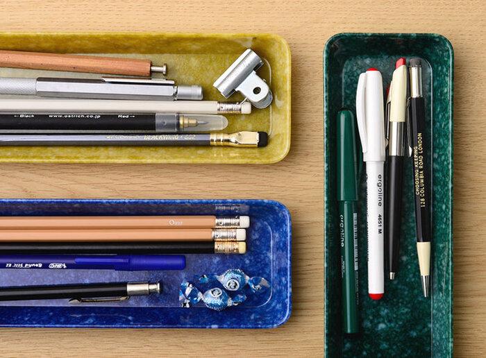 メラミン素材でできたマーブル模様が特徴のトレイには、ペンや鉛筆がピッタリ収まりスッキリとした印象に。探す手間なく取り出しやすくて、作業効率も上がりそう。用途別にトレイの色でわけるのもいいですね。