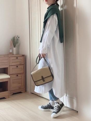 白のシャツワンピースの裾からデニムをチラ見せした、トレンド感のあるレイヤードスタイル。ローカットの黒のスニーカーなら、コンパクトにまとまりバランスよく着こなせます。