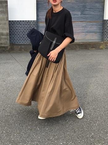 フレアロングスカートの足元に黒のスニーカーを合わせることで、かわいらしくなりがちなふんわりシルエットをきりりと引き締めています。スカート以外を黒でまとめて落ち着いた統一感のある着こなしに。