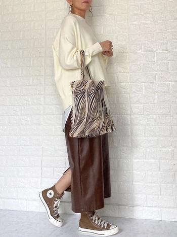 レザーのスカートにハイカットのブラウンスニーカーを合わせた着こなし。程よくカジュアルダウンしておしゃれな抜け感を作り出しています。