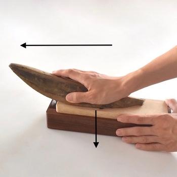 鰹節には頭と尾があります。細くくびれている頭を手前に向けて、奥へ押し出すように削りましょう。鰹節を少し立てて持つのがポイント。刃にしっかり当たるように、力を入れて削ります。もう片方の手で、削り器が動かないよう固定しましょう。