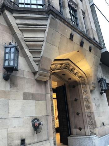細かい装飾が施された石造りのエントランスは、旧ビルの正面玄関の中央部分を保存したもの。建物の周囲はほぼガラスで、ごく一部だけですが当時の面影が今も残っています。
