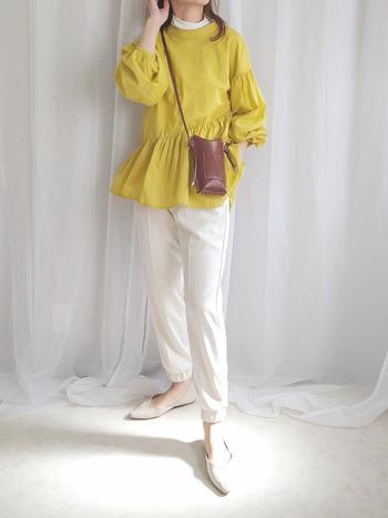 綺麗な黄色のペプラムブラウス。ボリューム袖と生地の斜めの切り替えラインがとても可愛いデザインですね。ボトムスやインナー、靴もホワイトでまとめることで、トップスのイエローが鮮やかに映えます。色の合わせ方が軽やかで、まさに「春」コーデ。