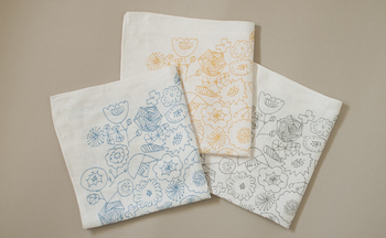清楚な白地に花畑をイメージして描かれたデザインのリネンハンカチです。1枚1枚職人の手によって刷られる「手捺染(てなっせん)」という製法を採用しているため、とても繊細で淡い色合いが魅力。