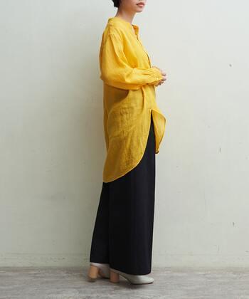 リネン100%の綺麗なイエローのバンドカラーシャツ。透け感があることで春らしい軽やかさと柔らかさをどちらも演出できるアイテムです。黒のワイドパンツでトップスの色を引き立てつつ、全体の印象をパキッと引き締めて。