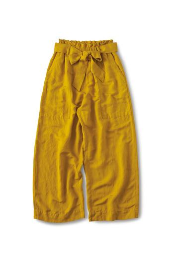ゆったりとした落ち着きのあるマスタード色のパンツ。春らしい麻レーヨンの生地のとろみとリボンで女性らしさを引き出してくれるおすすめの一本。気になるラインを隠し、足の形をきれいに見せてくれますよ。