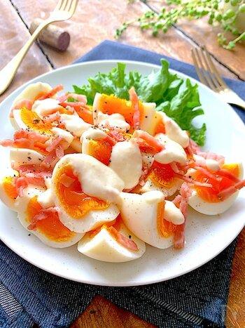 シーザーサラダ風のおつまみ卵。レンジ加熱するベーコンを全体に散らすようにしてから、マヨネーズドレッシングをかけると、見栄えが良くなります。  レタスや玉ねぎのスライスなどをたっぷり添えて、もっとサラダ仕立てにしてもいいですね。