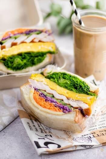 サラダチキンと卵焼きに、たっぷりの野菜が入ったボリューミーなサンドイッチ。紫キャベツとニンジンのカラフルさがポイント。