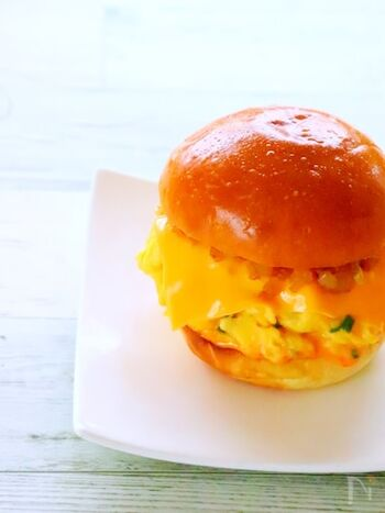 ハンバーガー用のパンを使ったエッグサンド。とろとろスクランブルエッグに、ピリ辛ソースがやみつきになるおいしさです。