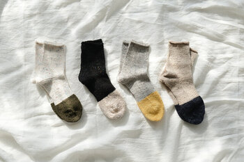 リネンとスラブコットンで編み上げた、履き心地の良い靴下。カラーネップが入っていて、落ち着いた色味の中に遊び心をこっそり忍ばせています。合わせやすいカラーはデイリーで使いやすく、靴を脱げばつま先の切り替えが可愛い優秀アイテム。