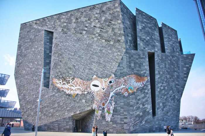 見上げるほど大きな建物は、建築家・隈研吾氏の設計。外壁に描かれているのは、幅24m×高さ10mもある「武蔵野皮トンビ」。牛革に描かれたトンビの体にカエルやカマキリなど多様な生き物や景色が散りばめられている独創的なデザインで、現代美術家の鴻池朋子氏が手掛けました。  「コロナ時代のアマビエ」プロジェクトの第2弾として今秋まで展示予定です。