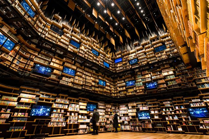 """5階建ての建物には、図書館・美術館・博物館が入っています。なかでも4階から5階にかけてある本棚は""""本棚劇場""""と呼ばれ、高さ8mに互い違いに組まれた中に約3万冊が所蔵されています。"""