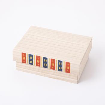 こけしは飾り台にもなる桐の箱に入っています。前面には矢羽の模様が描かれていて、華を添えています。19.5×20×14cmで、机の上にも置けるサイズです。