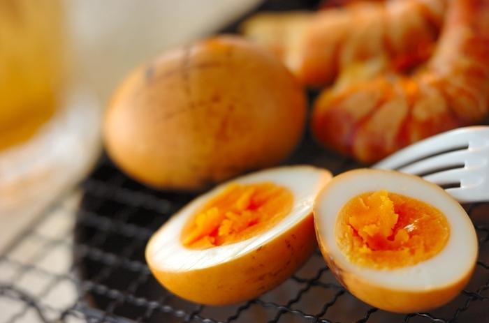 ゆで卵を燻製用のさくらチップで燻製にしたおつまみ卵です。ゆで卵は事前に、塩水に浸し、燻製にする前にしっかりと水分を拭き取ります。水分が残っていると、酸味が出てしまうそう。  好みの燻し加減が分かるまで、何度もチャレンジしたくなるひと品です。ビールやハイボールによく合いますよ。