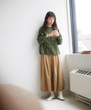 ベージュのロングスカートに、カーキのシャツを合わせたシンプルなコーディネートです。大人女子感のあるナチュラルスタイルは、足元の白靴下×シルバーシューズで程よく抜け感をプラスしているのがポイント。