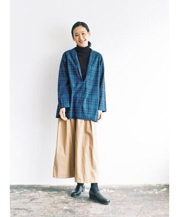 ベージュのスカートに、ブルーのチェックシャツを合わせたコーディネートです。深めのVネックデザインなので、中に黒のタートルネックを合わせて落ち着いた印象に。靴も黒で揃えて、季節感と大人感を両方アピールできる着こなしにまとめています。