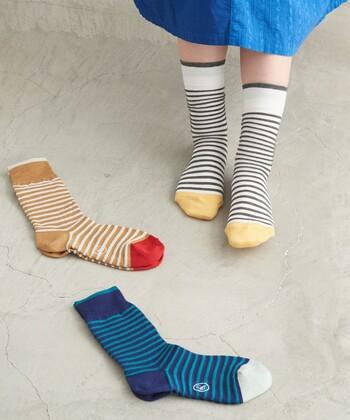 こちらは細いボーダー柄。二種類の糸を使って、ポコポコとした触り心地の編み地になっています。少しくしゅっとさせて履くとニュアンスのある柄に。つま先の配色が可愛いので、靴を脱いだ時も楽しめますね。