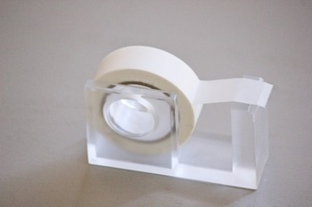 アクリル製の透明感が素敵な、外寸サイズ約7.5×2.3×4.5(cm)のミニテープ用のテープディスペンサー。
