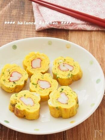 黄色のお花の形をした卵焼きは、串と輪ゴムで卵焼きに花の形づくっています。カニカマの赤もアクセント!片栗粉入りで冷めても美味しいのがポイントです。