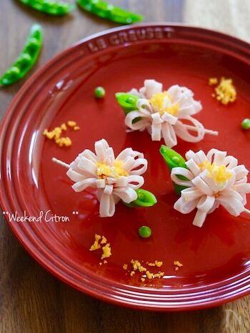 ハムで作ったピンク色のお花は、キッチンバサミで細かく切り込みを入れることで立体的な花びらを表現。中央にクリームチーズをのせることで、ざるで濾したゆで卵がくっつきやすくなり、味わいもアップします。