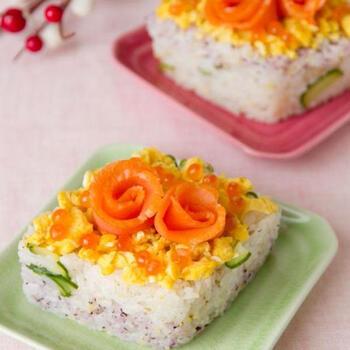 スモークサーモンをくるっと巻いて花に見立てたちらし寿司。そぼろ状のたまごやイクラをとっぴんうすることで華やかに。他のお刺身や生ハムでも応用できます。