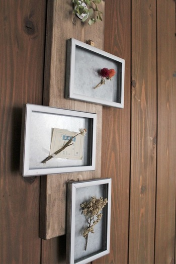 セリアのアルミフォトフレームを額縁として活用したアイデア。セリアのアイテムを2つ組み合わせてペイントし、木材に固定しています。フレームの中にドライフラワーを飾れば、ナチュラルなフラワーアートが完成。植物がひとつの作品として楽しめます。