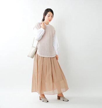 ベージュのニットベストに、透け感のあるチュールスカートを合わせたコーディネート。白のブラウスをレイヤードして、トレンド感と季節感をしっかりと押さえた着こなしにまとめています。