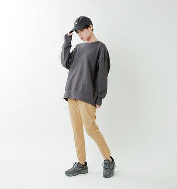 ベージュのランニングパンツに、グレーのスウェットを合わせたメンズライクなコーディネートです。黒のスニーカーとキャップをプラスして、とことんスポーティーな組み合わせにこだわった着こなしですね。