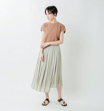 グリーンのプリーツスカートに、ベージュの半袖Tシャツをタックインしたスタイリングです。素足に黒のサンダルで、夏感たっぷりの涼しげなコーディネート。透け素材のカーディガンやシャツを羽織っても◎