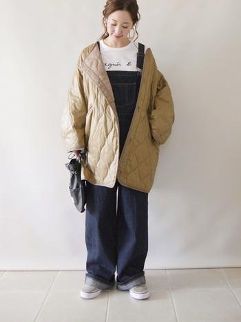 カジュアル感が強くなりがちなデニムのオーバーオールは、ベージュのキルティングコートで大人っぽさをプラス。ベージュのアウターをゆるく羽織って、抜け感を演出しているのもポイントですね。