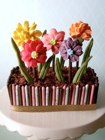 花壇に植えたお花のケーキ。土の部分はパウンドケーキを少しだけ細かくしてリアルさを表現しています。パウンドケーキの周りはポッキーで囲んで、カラフルな植木鉢に見立てて。お花好きな方へのプレゼントにしたらきっと喜んでくれるはず♪