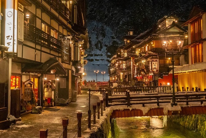 銀山温泉の街並みを形作る木造の建物は、一軒一軒少しずつおもむきが異なり、独特のノスタルジックな雰囲気を醸し出しています。昼は山々と青い空が映え、夜になればレトロなガス灯が街並みを照らし出し、昼と夜どちらも楽しめるのが魅力。冬になれば雪がつもり、また違った顔を見せてくれます。