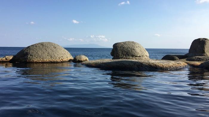 """北川温泉の中でも、特に海に近い距離で温泉を楽しめるのが黒根岩風呂です。黒根岩風呂は波打ち際のすぐそばにある公営の露天風呂で、湯舟につかると温泉が海と一体になっているかのよう。波の高い日には波しぶきが飛んでくることもあり、開放感と迫力は満点です。太平洋を水平線まで見通すことができるので、黒根岩風呂は""""アメリカを見ながら入る野天風呂""""とも言われています。"""