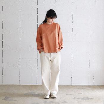 白のストレートデニムに、シンプルなオレンジトップスを合わせたコーディネートです。あえてタックインせずにサラッと着こなすことで、大人のナチュラル感を演出しています。足元は白のスニーカーで、カジュアルなベーシックコーデに。