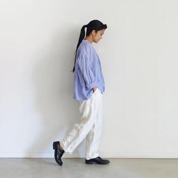 白のワイドデニムパンツに、青のブラウスを合わせたコーディネートです。シャツやブラウスをタックインするときちんとコーデになりますが、あえて裾を出すと程よくラフな着こなしに。足元は黒のシューズで、爽やかなカラーリングに引き締めポイントをプラスしています。
