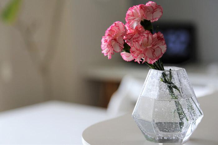 ニトリのグラスベースに活けたカーネーション。気泡入りのガラスがみずみずしい印象で、シンプルながらお花を引き立ててくれます。キッチンカウンターの一角に置けば、料理中でも花を楽しめますね。