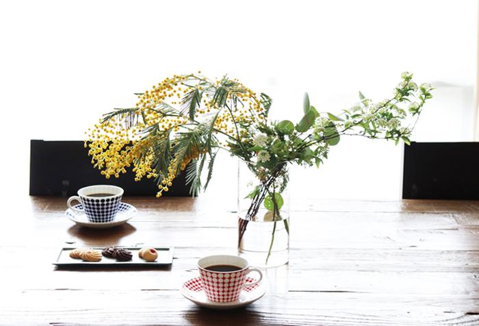 テーブルの真ん中にどんと置いたミモザの花瓶。枝ものと一緒に活けるとボリューム感がアップしてインテリアのアクセントになりますね。食事やお茶をしながらお花を眺める素敵な時間を過ごせます。