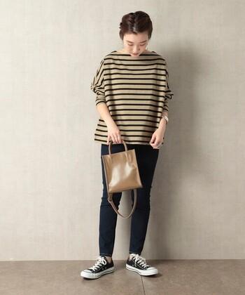 大人っぽく着こなせるベージュのボーダートップスに、ネイビーのスキニーデニムを合わせたコーディネートです。バッグもベージュ系で色を揃えているのがポイント。足元はスニーカーで、大人カジュアルなテイストに。