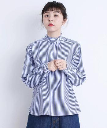 フリルのスタンドカラーがガーリーなシャツ。ストライプ柄なので甘くなりすぎませんね。