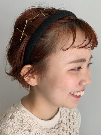 ショートヘアにレトロなかわいらしさを演出してくれるカチューシャ。広がってしまう部分の毛を束にして軽くねじり、ヘアピンでランダムに留めています。