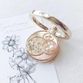 ゴールドのワイヤーパーツに押し花やパールで泡を描いたデザイン。上品に優しくきらめくジュエリーのようなスマホリングです。
