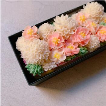 """和菓子派にも洋菓子派にもおすすめなのが、7D Sweetsのケーキ。""""あんフラワーケーキ""""というジャンルで、抹茶&プレーンのパウンドケーキをベースに、あんこで作った立体的なお花がデコレーションされています。口金を使った繊細な花びらが見事。桃やピンポンマムなど、春らしいお花が満開です。"""