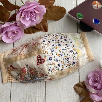 テイストの違う花模様の布をパッチワークで合わせたマスクです。  無地の布を間に合わせることで、隣の柄への移行がスムーズになっています。ナチュラルな色味で、洋服にもコーディネートしやすいマスクです。