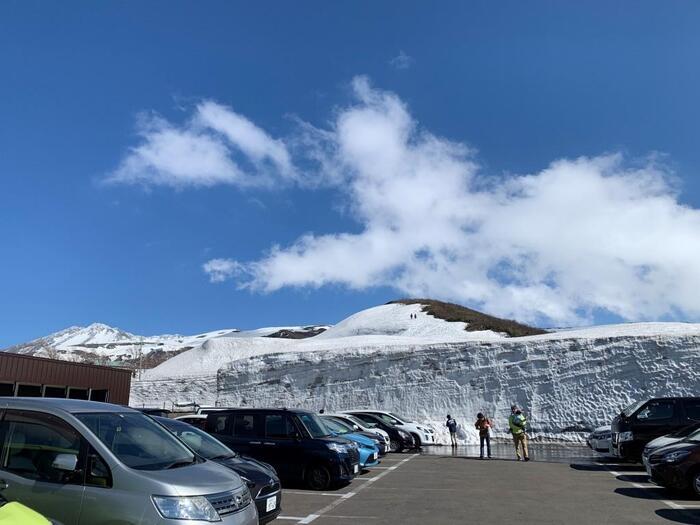 鳥海山は海に近い場所にあるため、街を飛び越えて海が見えます。大地の広さはもとより、地球の大きさも感じる壮大な景色ですよ。空が赤と紫のグラデーションに染まるマジックアワーの景色もおすすめ。また、鳥海ブルーラインも雪の回廊ができる道路で、とくに頂上の鉾立展望台付近には長く雪が残っています。