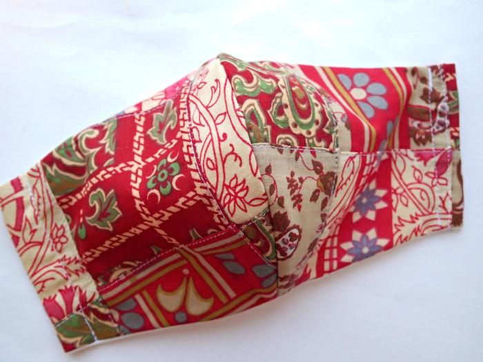 ペイズリーやボタニカルの布をつないだパッチワーク・マスクです。  赤をテーマに集めたピース。同じ柄の布を繰り返し配することで、全体をうまくひとつにまとめています。