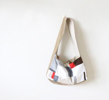 白、黒、グレー、赤とスタイリッシュな色味で構成されたリネンのパッチワーク・バッグです。  白のピースの面積を大きく取り、黒や赤をアクセント的に使っています。ショルダーとマチ部分には帆布を使い、丈夫さもプラス。カジュアルな装いにぴったりのバッグに仕上がりました。