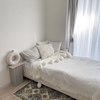 ホワイトと淡いグレーでまとめられたベッド周り。ベッドの小ささを感じないのは、ほどよいボリューム感があるからでしょうか。たくさん並んだクッションや、モダンなオブジェが雰囲気にぴったりとハマっています。